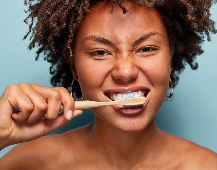 lady brushing teeth with bamboo brush