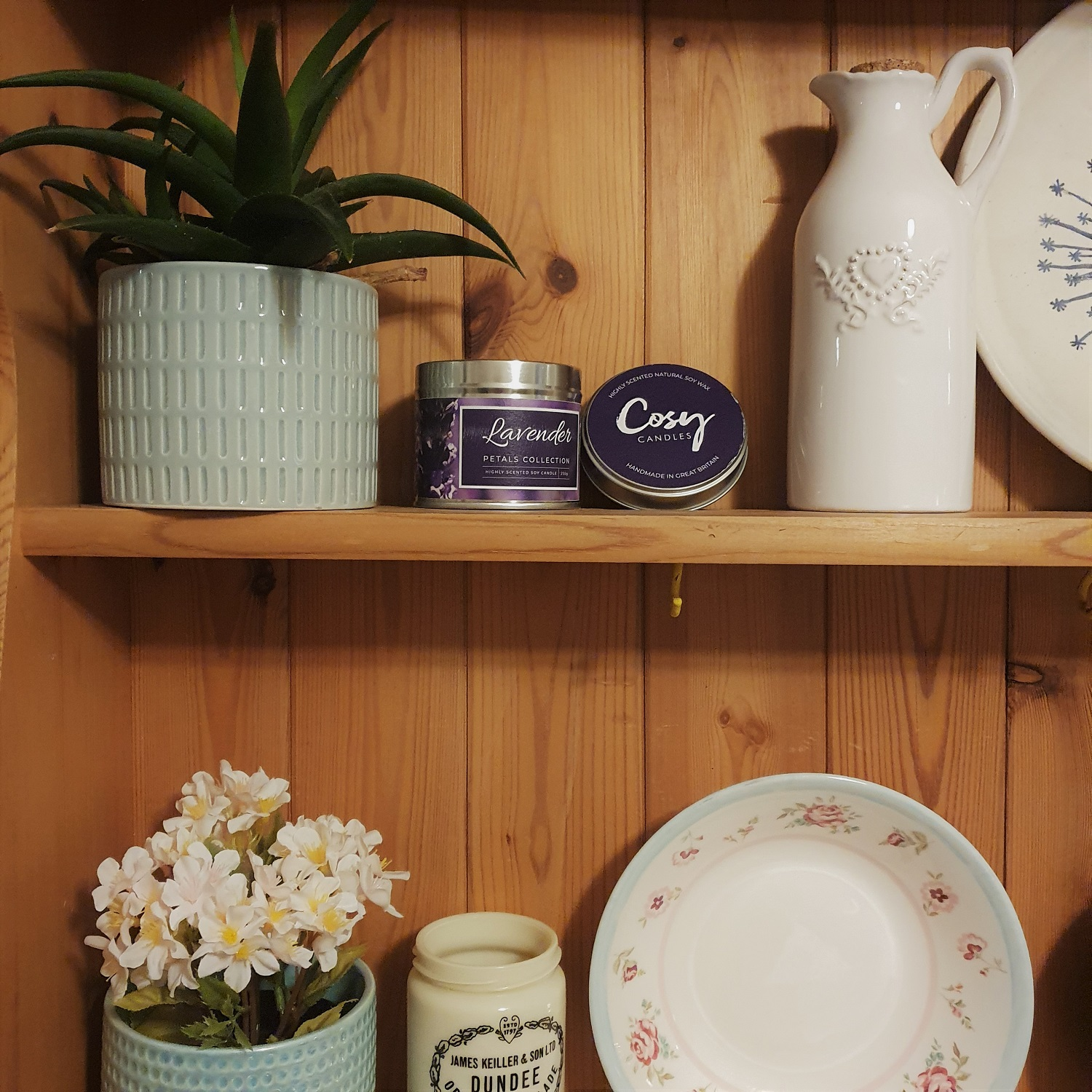 A shelf with assorted home decor and a Cosy Aromas candle